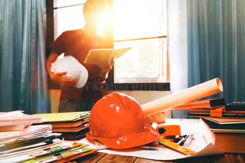 Bedrijfsingenieur die hard bij zijn bureau in bui van het flathuis werken royalty-vrije stock afbeelding