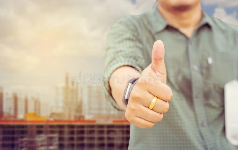 Bedrijfsingenieursmens die duim opgeven als teken van Succes over bl stock foto