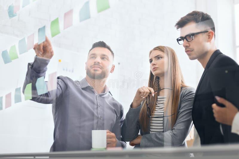 Bedrijfsinvesteerders die het werk bespreken die nota's bekijken royalty-vrije stock afbeeldingen