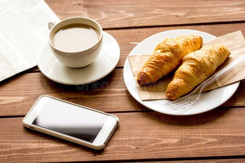 Bedrijfskop van koffie met croisant en telefoon op bureau royalty-vrije stock afbeelding