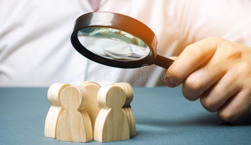 Bedrijfsleider die een vergrootglas over een team van arbeiders houden Het concept het vinden van nieuwe werknemers Teamliding te stock foto