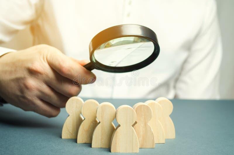 Bedrijfsleider die een vergrootglas over een team van arbeiders houden Het concept het vinden van nieuwe werknemers Teamliding te stock fotografie