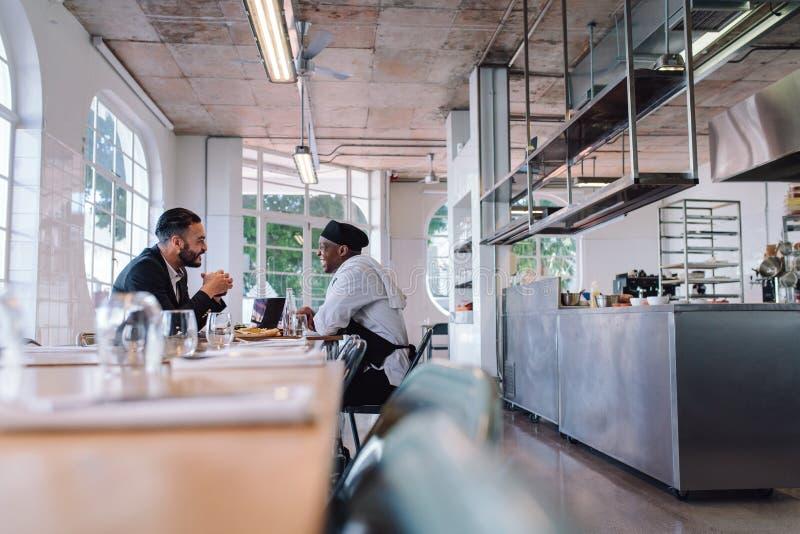 Bedrijfsleider en chef-kok die in restaurant spreken royalty-vrije stock afbeelding
