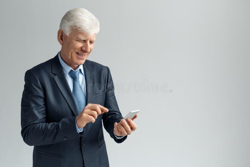 Bedrijfslevensstijl Zakenman die bij het grijze het doorbladeren smartphone blij lachen wordt zich geïsoleerd bevinden die royalty-vrije stock afbeelding
