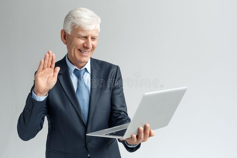 Bedrijfslevensstijl Zakenman status geïsoleerd op grijs hebbend videogesprek op laptop die aan vriendschappelijke camera golven royalty-vrije stock fotografie