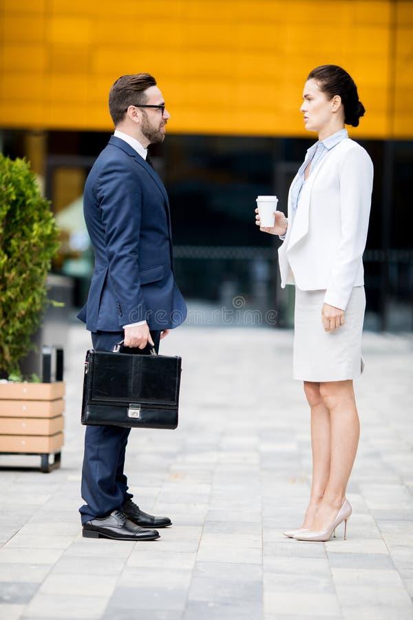 Bedrijfsman en vrouw die dialoog over onderbreking hebben royalty-vrije stock afbeelding