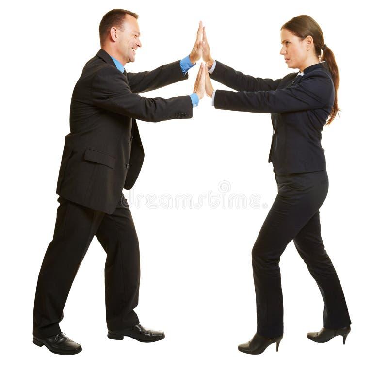 Bedrijfsman en vrouwen duwende handen stock foto
