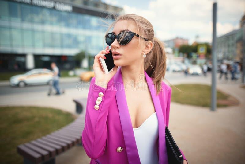 Bedrijfsmeisje die op de telefoon op de straat spreken royalty-vrije stock afbeeldingen