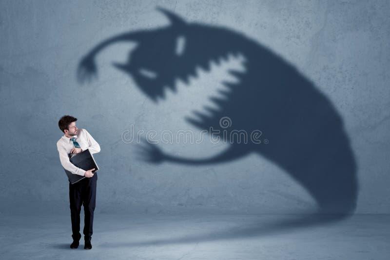 Bedrijfsmens bang van zijn eigen concept van het schaduwmonster royalty-vrije stock afbeeldingen