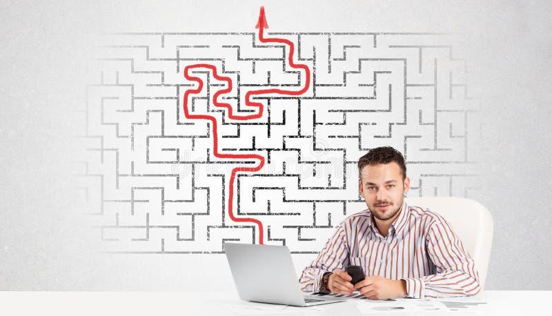 Bedrijfsmens bij bureau met labyrint en pijl royalty-vrije stock foto's