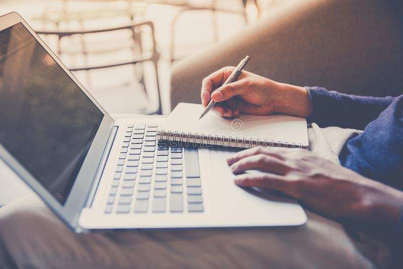 Bedrijfsmens die aan laptop computer en het schrijven notitieboekje werken stock afbeeldingen