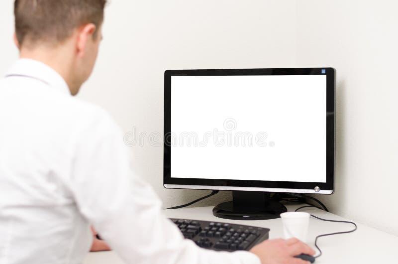 Bedrijfsmens die achter een computer met het witte scherm werkt stock foto