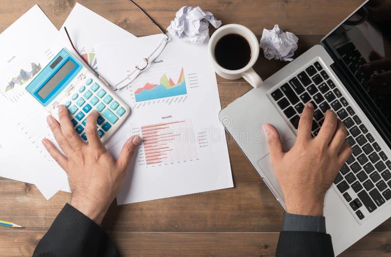 Bedrijfsmens die computer en calculator op lijst gebruiken stock foto's