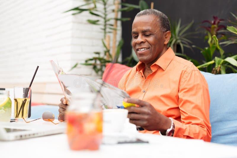 Bedrijfsmens die de krant lezen bij een koffiewinkel stock foto