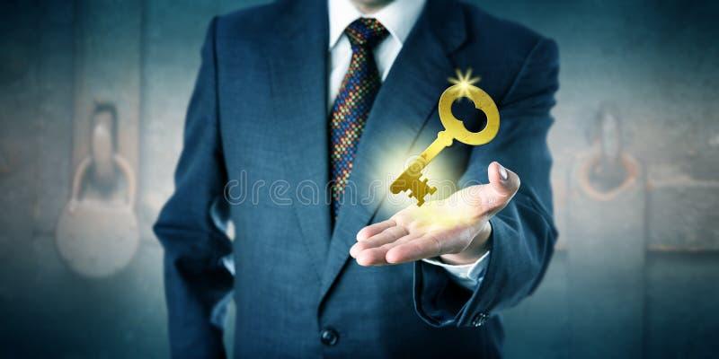 Bedrijfsmens die een Gouden Sleutel in Open Palm aanbieden stock foto's