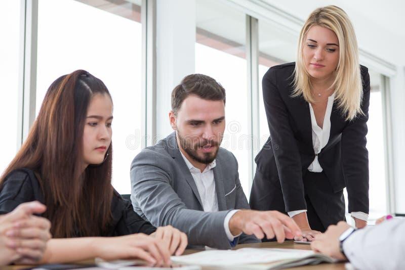 bedrijfsmens die en op het grafiek of documentdocument in vergaderzaal voorstellen richten Groep jonge bedrijfsmensenbrainstormin royalty-vrije stock foto's