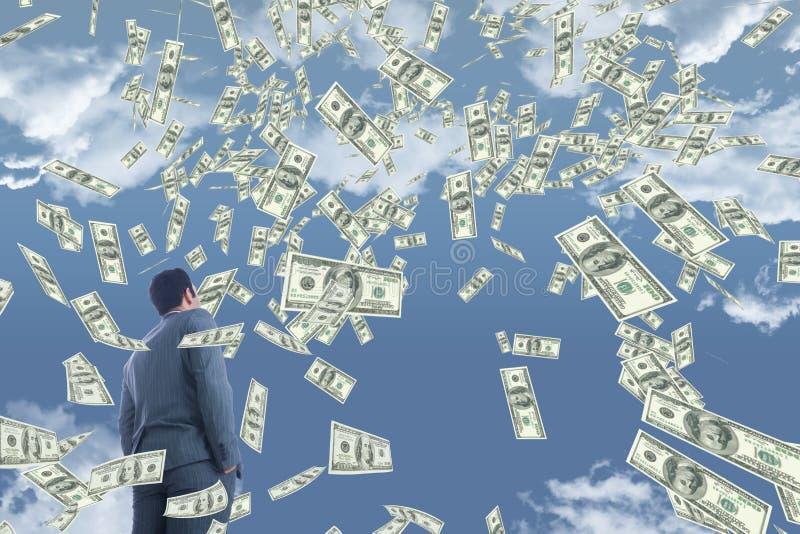 Bedrijfsmens die geldregen tegen hemel met wolken bekijken stock foto's