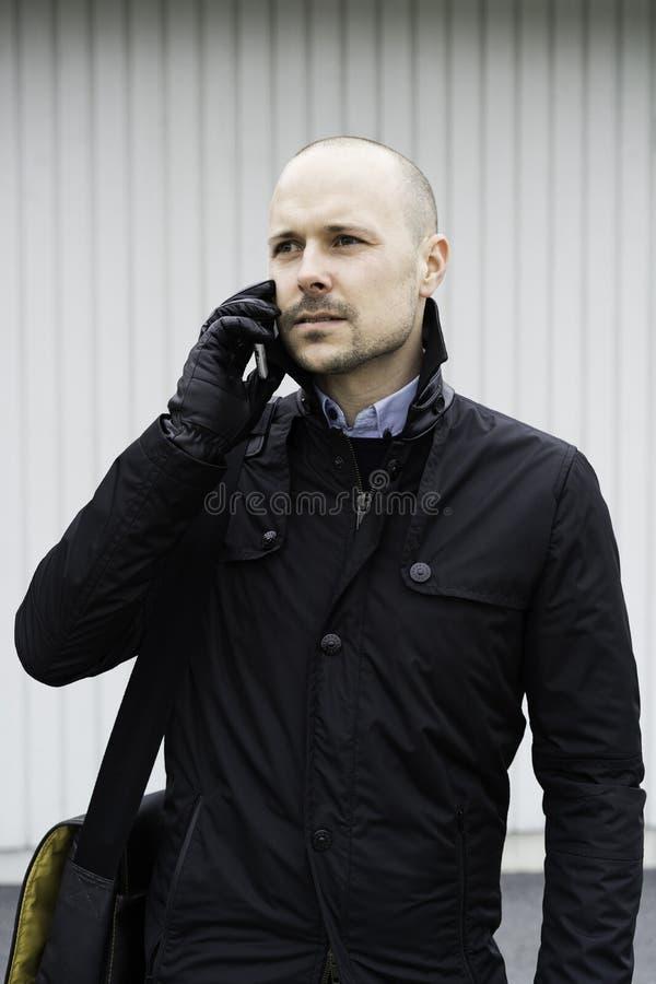 Bedrijfsmens die het openlucht spreken in telefoon bevinden zich royalty-vrije stock afbeelding