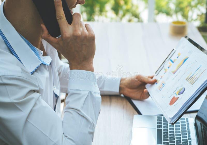 Bedrijfsmens die het rapport bij de telefoongesprekmededeling controleren royalty-vrije stock foto
