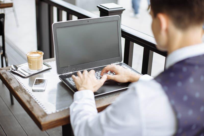 Bedrijfsmens die laptop in koffiewinkel met behulp van royalty-vrije stock afbeeldingen