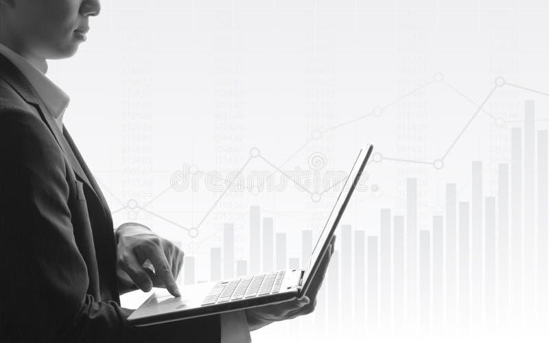 Bedrijfsmens die laptop met abstracte financiële grafiek en uptrend lijngrafiek met behulp van in effectenbeurs op zwart-witte kl stock foto