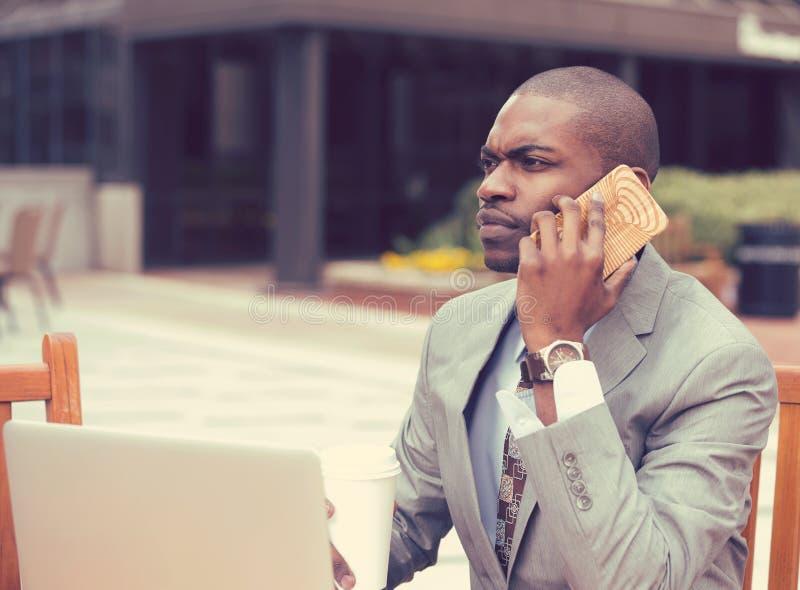 Bedrijfsmens die met laptop die in openlucht aan mobiele telefoon werken spreken stock afbeelding