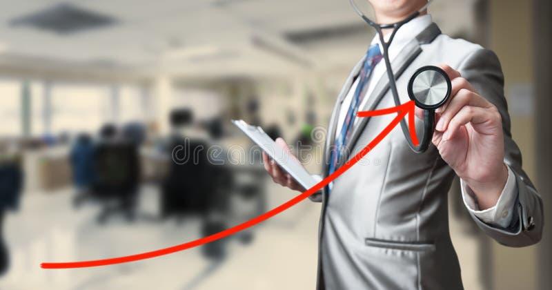 Bedrijfsmens die met stethoscoop rode kromme onderzoeken stock afbeelding