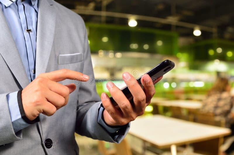 Bedrijfsmens die mobiele slimme telefoon in Restaurant of Voedsel Cour met behulp van royalty-vrije stock afbeelding