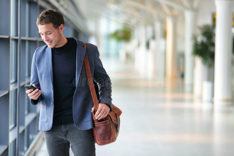 Bedrijfsmens die mobiele telefoon app in luchthaven met behulp van stock fotografie