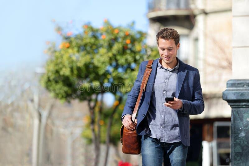 Bedrijfsmens die mobiele telefoon met behulp van die aan het werk lopen royalty-vrije stock fotografie