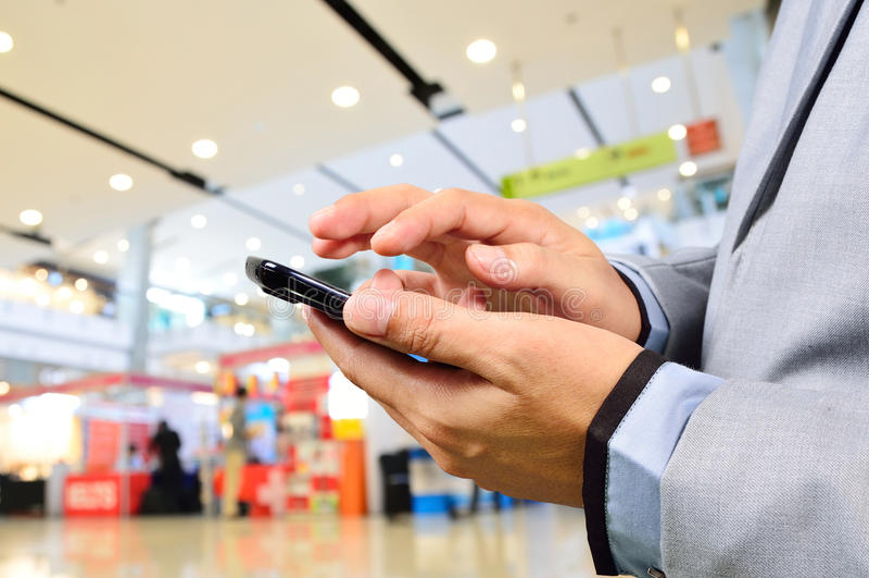 Bedrijfsmens die Mobiele Telefoon in Modern Winkelcomplex met behulp van royalty-vrije stock foto's