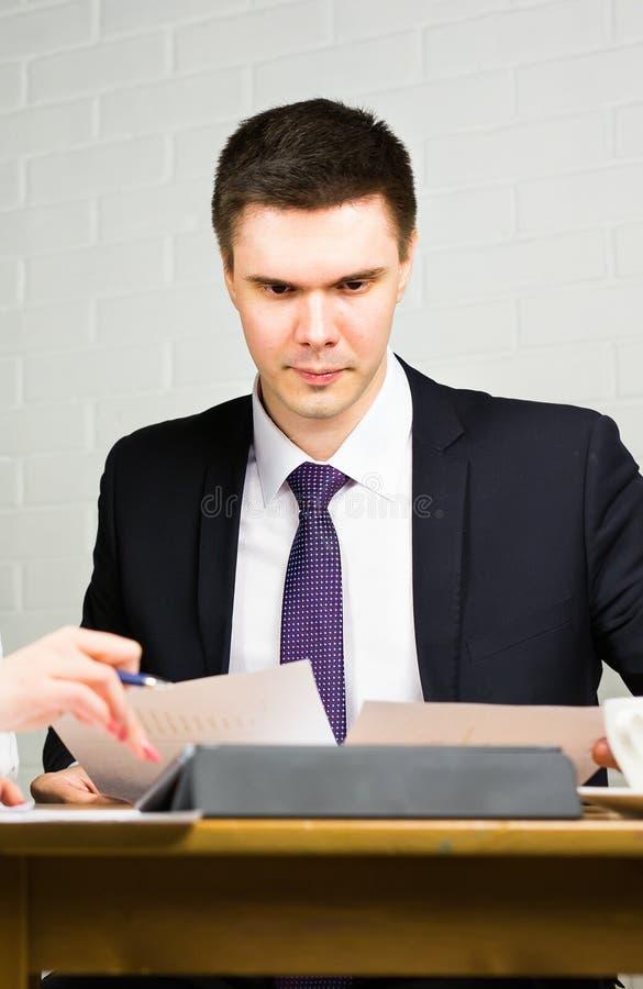 Bedrijfsmens die op kantoor met documenten aan zijn bureau, het concept van de adviseuradvocaat werken stock foto's