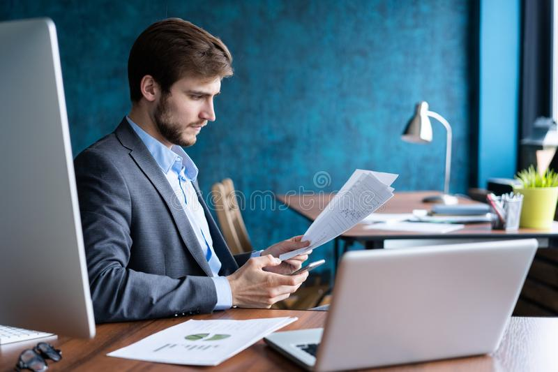 Bedrijfsmens die op kantoor met laptop en documenten aan zijn bureau, het concept van de adviseuradvocaat werken stock foto's
