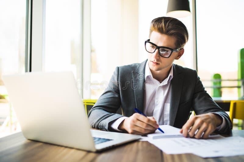 Bedrijfsmens die op kantoor met laptop en documenten aan zijn bureau werken royalty-vrije stock foto's