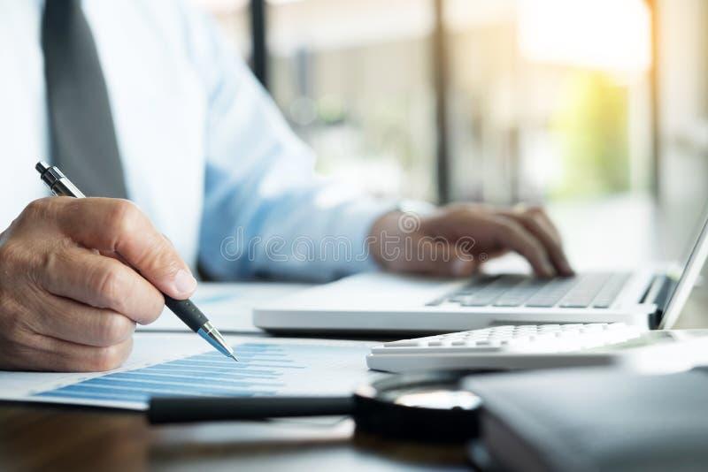 Bedrijfsmens die op kantoor met laptop, tablet en grafiek werken dat royalty-vrije stock foto's