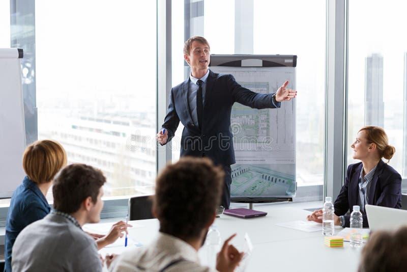 Bedrijfsmens die over project tijdens vergadering spreken stock afbeelding