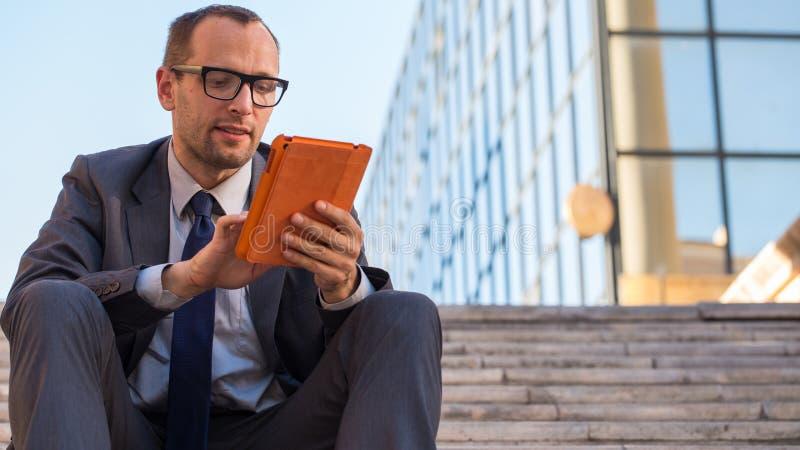 Bedrijfsmens die tabletpc in oranje dekking op een stadsstraat met behulp van. stock fotografie