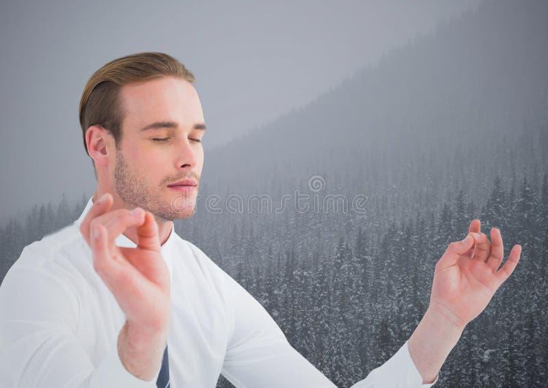 Bedrijfsmens die tegen heuvels met bomen en grijze hemel mediteren stock afbeelding