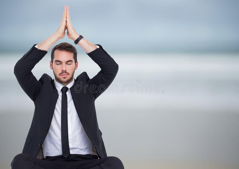 Bedrijfsmens die tegen onscherp strand mediteren stock fotografie
