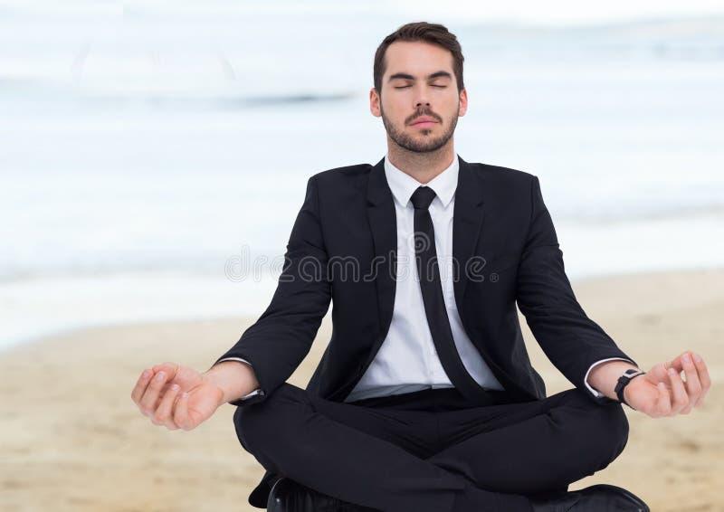 Bedrijfsmens die tegen onscherp strand mediteren stock afbeelding
