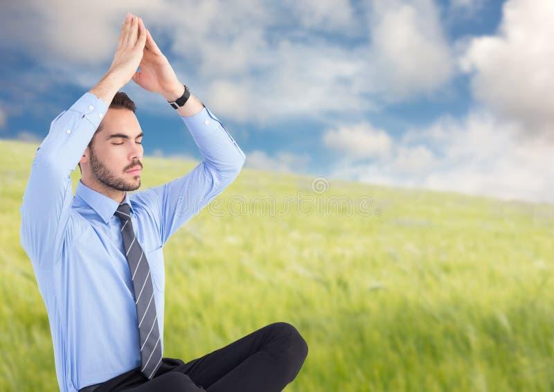 Bedrijfsmens die tegen onscherpe weide mediteren royalty-vrije stock afbeelding