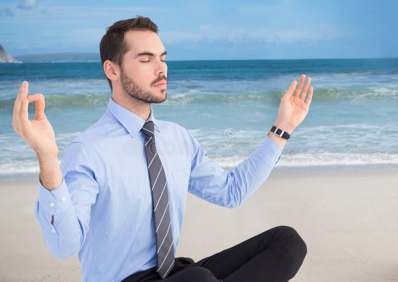 Bedrijfsmens die tegen strand mediteren stock foto's