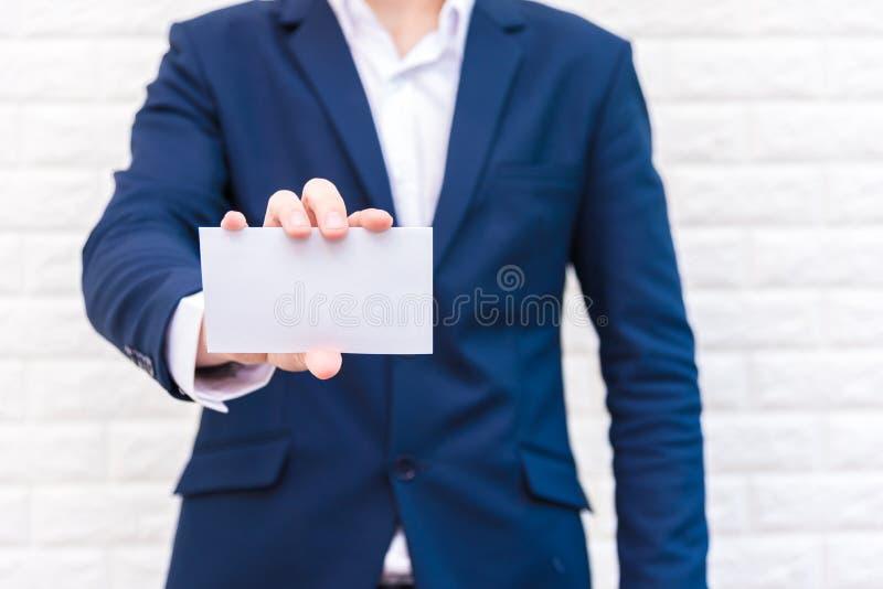 Bedrijfsmens die Witboek tonen Mens die blauw kostuum dragen en witte lege kaart houden Levensstijl en het werk concept Zaken en royalty-vrije stock fotografie