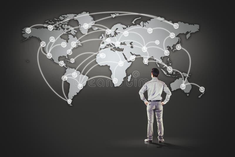 Bedrijfsmens die zich voor wereldkaart bevinden stock illustratie