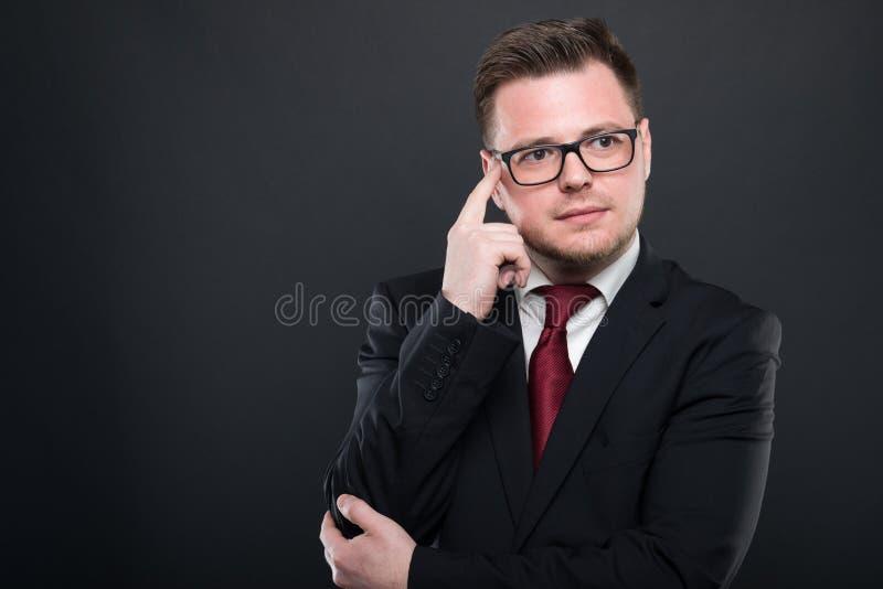 Bedrijfsmens die zwart kostuum dragen die het denken gebaar maken royalty-vrije stock foto