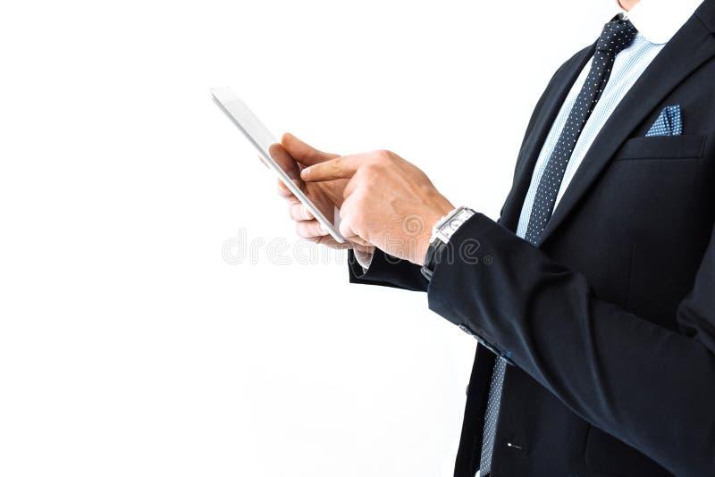 Bedrijfsmens, in een kostuum en glazen, die aan een digitale tablet werken stock foto's