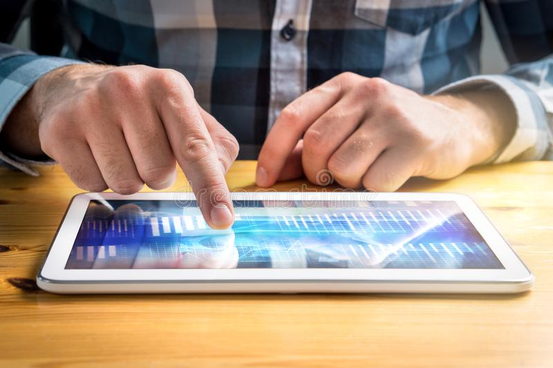Bedrijfsmens gebruikend tablet en bekijkend financiële grafieken royalty-vrije stock afbeeldingen