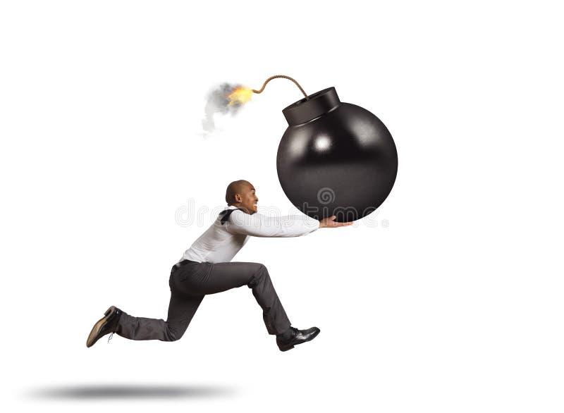 Bedrijfsmens in gevaarslooppas met een grote bom in zijn hand stock fotografie