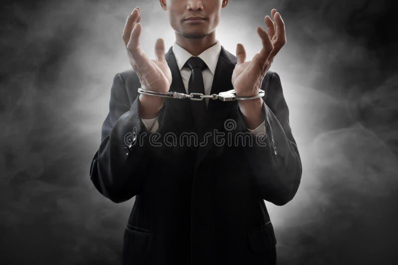Bedrijfsmens in handcuffs op rookachtergrond stock afbeeldingen