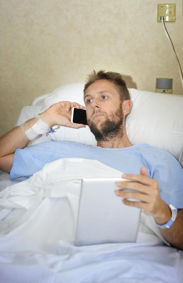 Bedrijfsmens in het ziekenhuisruimte die in bed het zieke en verwonde werken met mobiele telefoon en digitaal stootkussen liggen royalty-vrije stock foto's